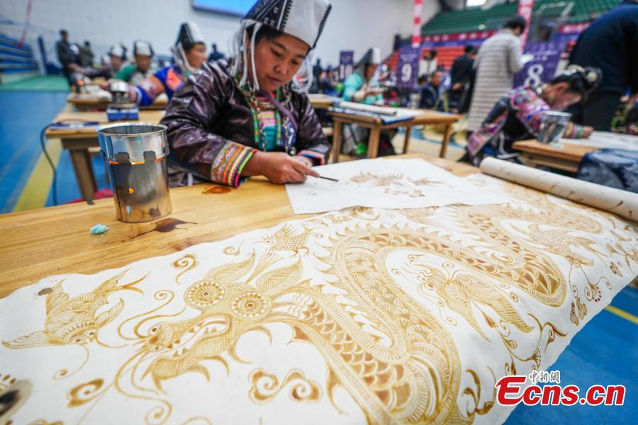 A competitor presents wax printing skills during a manual skills competition held in Rongjiang County of Qiandongnan Miao and Dong Autonomous Prefecture, southwest China\'s Guizhou Province, on Nov. 15, 2018. A number of artisans from the county participated in the competition in aspects of spinning, weaving, wax printing, embroidery and so on.(Photo: China News Service/ He Junyi)
