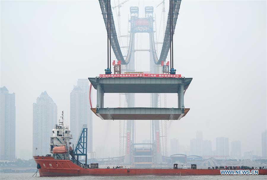 A 1,000-tonne steel beam is lifted to be installed at the construction site of the Yangsigang Bridge across the Yangtze River in Wuhan, capital of central China\'s Hubei Province, on Nov. 15, 2018. Construction of a double-deck suspension bridge with the longest span in the world is expected to be completed in October 2019, said an engineer working on the project. The bridge, with a 1,700-meter-long main span across the Yangtze River in Wuhan, saw the first steal beam installed for the bridge deck Thursday. (Xinhua/Cheng Min)