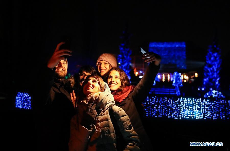 Visitors take selfies in front of light decorations during the \
