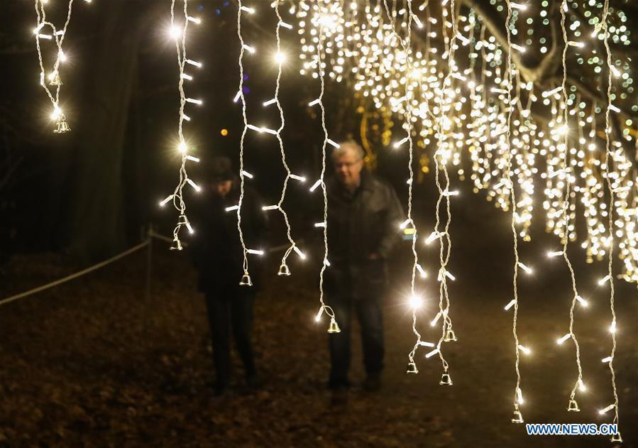 Two visitors walk under light decorations during the \
