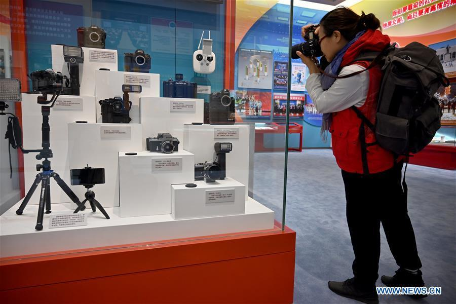 A visitor takes pictures of vintage cameras once used by Xinhua News Agency photographers which are displayed at a major exhibition to commemorate the 40th anniversary of China\'s reform and opening-up at the National Museum of China in Beijing, capital of China, Nov. 15, 2018. Vintage objects are displayed at the exhibition which opened here on Tuesday to show visitors the history, accomplishments, and experience of China\'s reform and opening-up. (Xinhua/Li Xin)