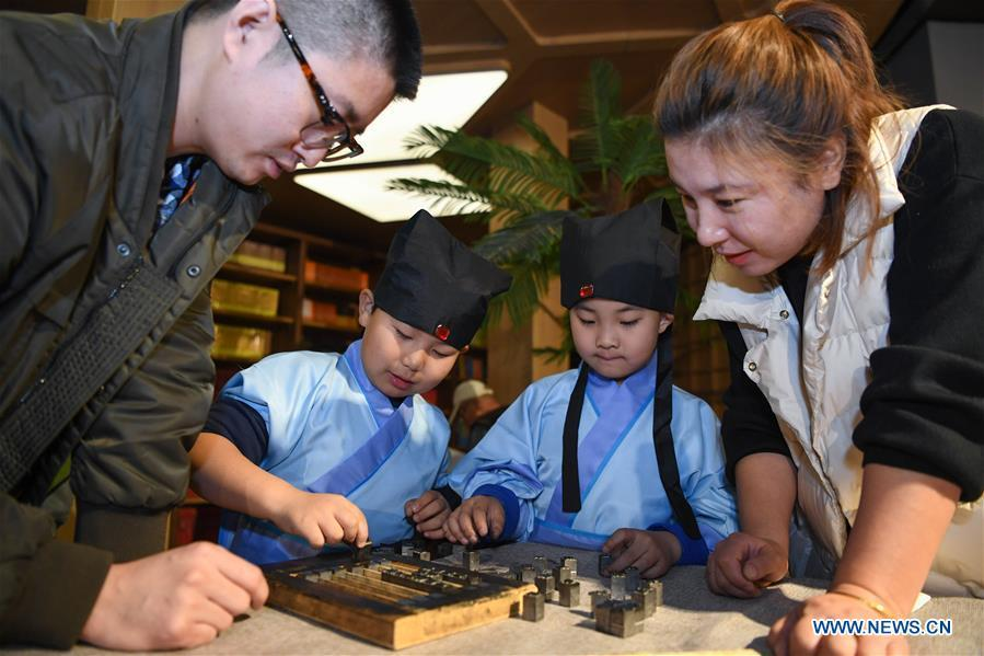Primary school students experience the processes of movable-type printing in Shenyang, capital of northeast China\'s Liaoning Province, Nov. 18, 2018. (Xinhua/Long Lei)
