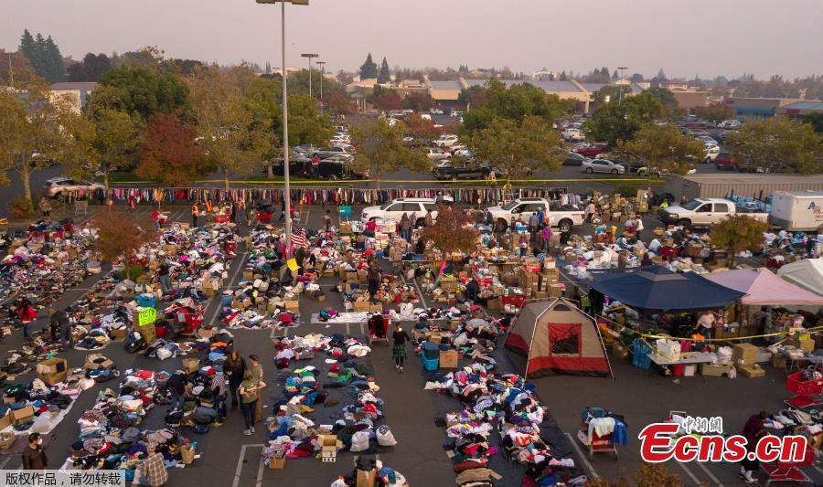 Fire evacuees sift through a surplus of donated items in a parking lot in Chico, California on November 17, 2018. More than 1,000 people remain listed as missing in the worst-ever wildfire to hit the US state.  (Photo/Agencies)