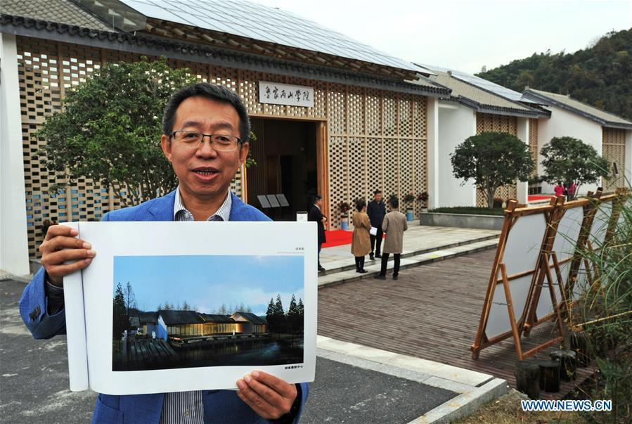 Ding Wei, a designer from south China\'s Guangdong Province, shows the effect picture of a building in Lujia Village of Anji County, east China\'s Zhejiang Province, Nov. 14, 2018. Lujia Village is located in the mountainous region in northeastern Anji. The village has a population of over 2,200 and about 533 hectares of bamboo forests. To build a beautiful village and improve the living of local villagers, Lujia implemented a comprehensive plan for rural, industrial and tourism development in recent years. The income of the village\'s collective economy surged from 18,000 yuan (about 2,500 U.S. dollars) in 2011 to 3.3 million yuan (about 475,000 U.S. dollars) in 2017. The per capita income of local people arrives at 35,000 yuan (about 5,000 U.S. dollars). So far, the village has collective assets valued at nearly 200 million yuan (about 28.8 million U.S. dollars). (Xinhua/Tan Jin)