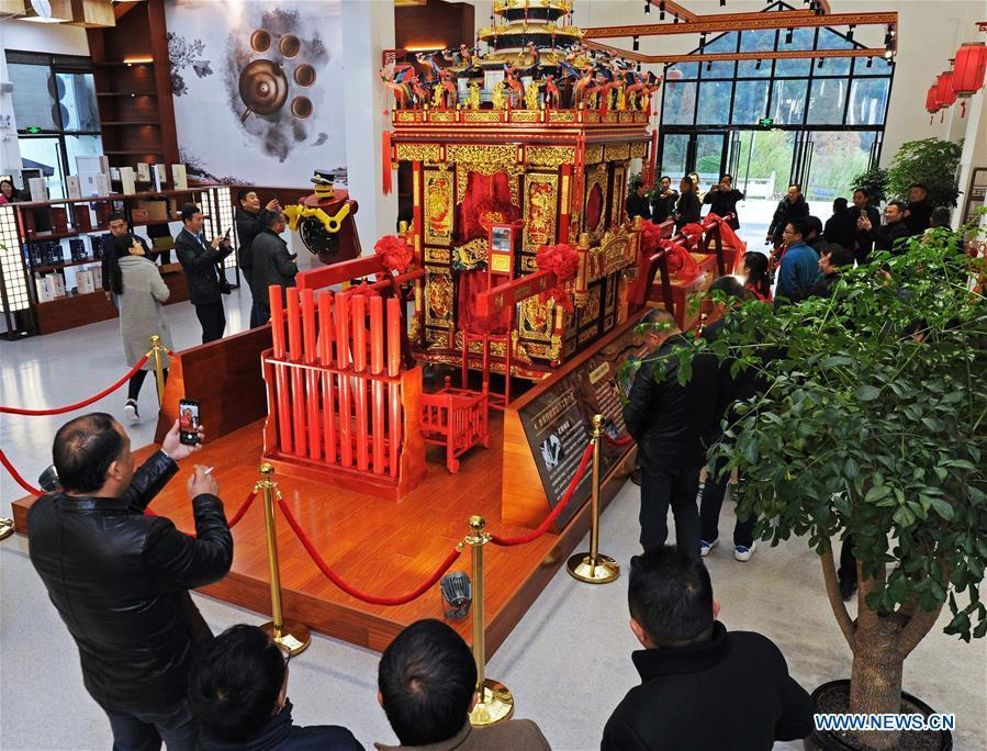Tourists view a traditional sedan chair made by local carpenter Guo Jinxian in Lujia Village of Anji County, east China\'s Zhejiang Province, Nov. 16, 2018. Lujia Village is located in the mountainous region in northeastern Anji. The village has a population of over 2,200 and about 533 hectares of bamboo forests. To build a beautiful village and improve the living of local villagers, Lujia implemented a comprehensive plan for rural, industrial and tourism development in recent years. The income of the village\'s collective economy surged from 18,000 yuan (about 2,500 U.S. dollars) in 2011 to 3.3 million yuan (about 475,000 U.S. dollars) in 2017. The per capita income of local people arrives at 35,000 yuan (about 5,000 U.S. dollars). So far, the village has collective assets valued at nearly 200 million yuan (about 28.8 million U.S. dollars). (Xinhua/Tan Jin)