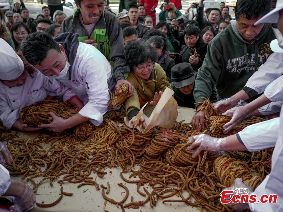 A 59-kilogram mahua, or fried dough twist is shown during a cultural festival in north China\'s city of Tianjin, November 18, 2018. Made of flour, sesame, walnut, peanuts and sweet-scented osmanthus, the snack usually comes deep fried. A variety of flavors are available regardless if you prefer to eat sweet or salty. (Photo: China News Service/ Tong Yu)