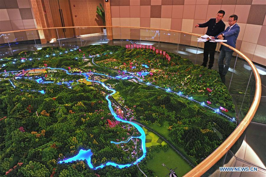 Zhu Renbin (L), secretary of the Communist Party of China local branch in Lujia Village, discusses the village\'s development plan with Ding Wei, a designer from south China\'s Guangdong Province, in Lujia of Anji County, east China\'s Zhejiang Province, Nov. 14, 2018. Lujia Village is located in the mountainous region in northeastern Anji. The village has a population of over 2,200 and about 533 hectares of bamboo forests. To build a beautiful village and improve the living of local villagers, Lujia implemented a comprehensive plan for rural, industrial and tourism development in recent years. The income of the village\'s collective economy surged from 18,000 yuan (about 2,500 U.S. dollars) in 2011 to 3.3 million yuan (about 475,000 U.S. dollars) in 2017. The per capita income of local people arrives at 35,000 yuan (about 5,000 U.S. dollars). So far, the village has collective assets valued at nearly 200 million yuan (about 28.8 million U.S. dollars). (Xinhua/Tan Jin)