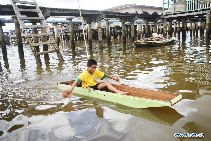 A boy plays in a self-made boat at the Water Village in Bandar Seri Begawan, capital of Brunei, on Nov. 18, 2018. (Xinhua/Wang Shen)