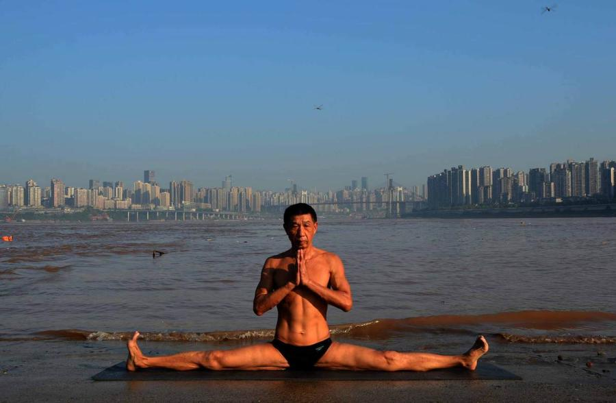 Wang Wanming, 61, a retiree in Southwest China\'s Chongqing municipality, has been practicing yoga almost every day by the Yangtze River for six years. His technique has made him a local celebrity. (Photo provided to chinadaily.com.cn)
