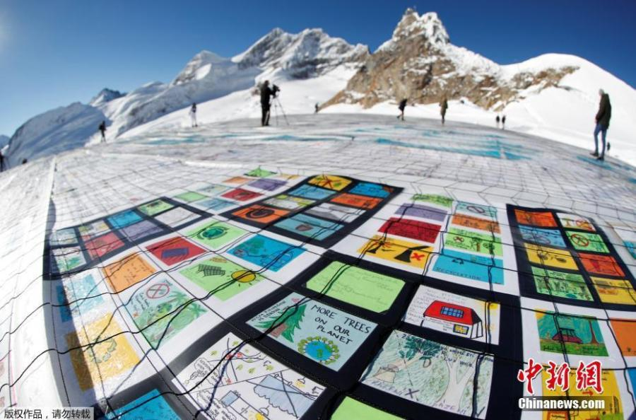 A giant postcard of approximately 2500 square meters made of contributions from over 125\'000 individual postcards containing messages aiming to fight climate change and global warming, is pictured on the Aletsch glacier near the Jungfraujoch saddle by the Jungfrau peak, in Switzerland, Nov 16, 2018. (Photo/Agencies)