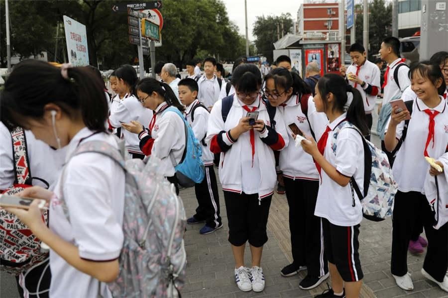 Students peer at their mobile phones while waiting to cross the road at Dongdaqiao in Beijing\'s Chaoyang district, Sept 18, 2018. (Photo provided to chinadaily.com.cn)