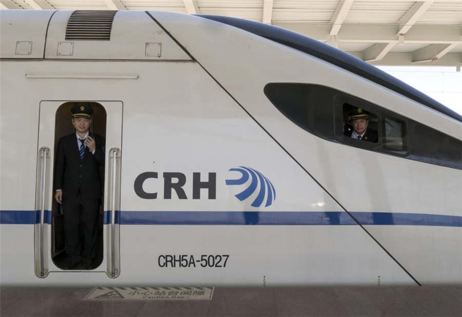 A train engineer peers out the door of the CRH5A high-speed train in Hunchun city, Northeast China\'s Jilin Province, April 27, 2018. (Photo provided to chinadaily.com.cn)