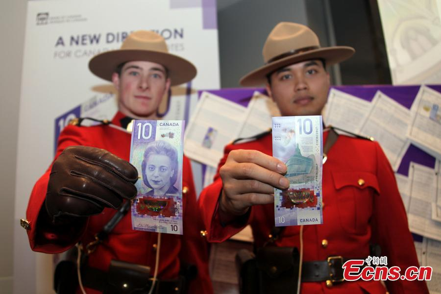 People hold a $10 banknote featuring Viola Desmond in Toronto, Canada, Nov. 19, 2018. The banknote is the first vertically oriented bill in Canada and the first regularly circulating banknote to feature a Canadian woman, civil rights advocate Viola Desmond, on the front. (Photo: China News Service/Yu Dongrui)