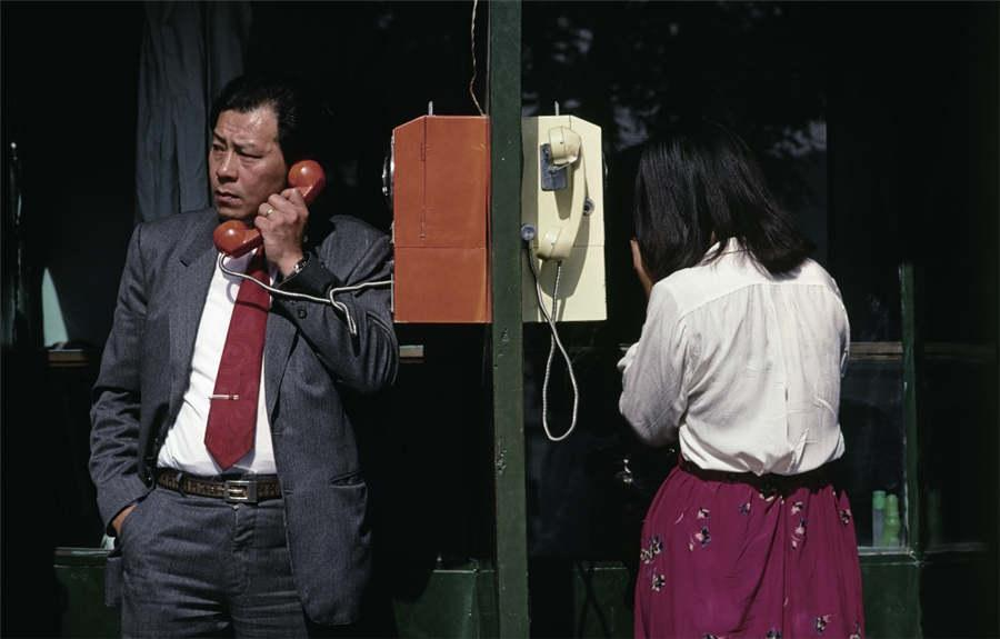People use a telephone box by a road in Qianmen, Beijing, 1987 (Photo provided to chinadaily.com.cn)