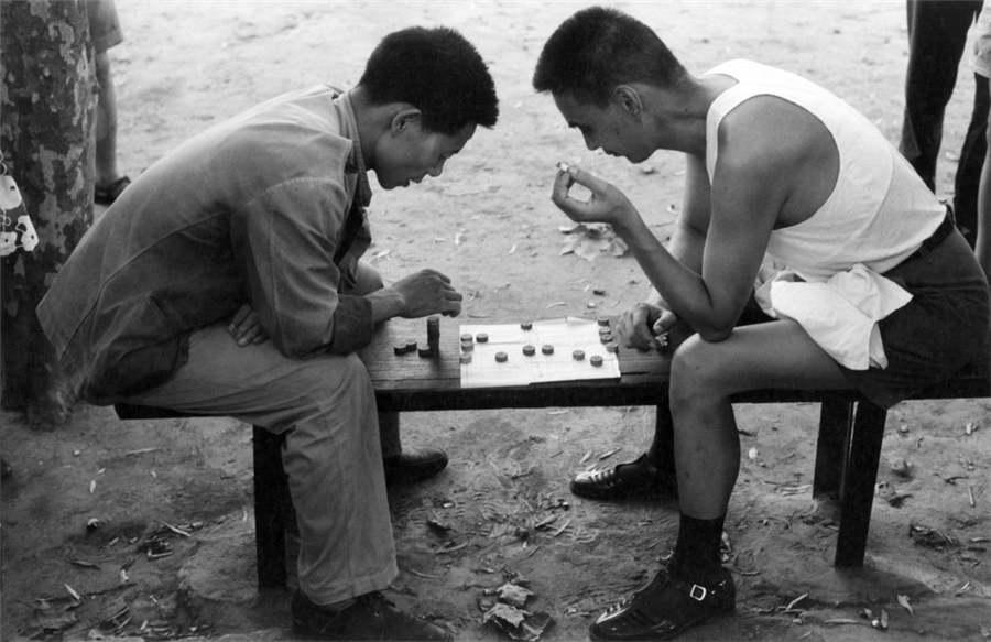 Two men play chess on a bench in Shanghai, 1971.  (Photo provided to chinadaily.com.cn)
