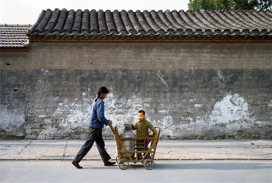 A woman pushes a child in a cart in Beijing, 1979. (Photo provided to chinadaily.com.cn)