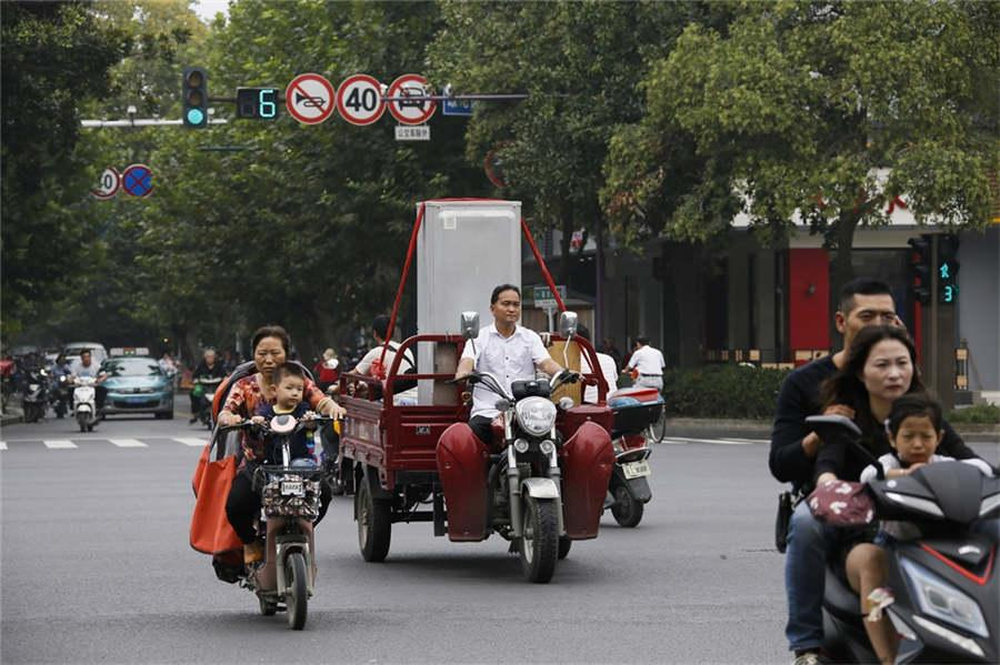 A man carries a refrigerator in a three-wheeled scooter on Guoqing Road, Yangzhou city, East China\'s Jiangsu province, Sept 22, 2018.  (Photo provided to chinadaily.com.cn)