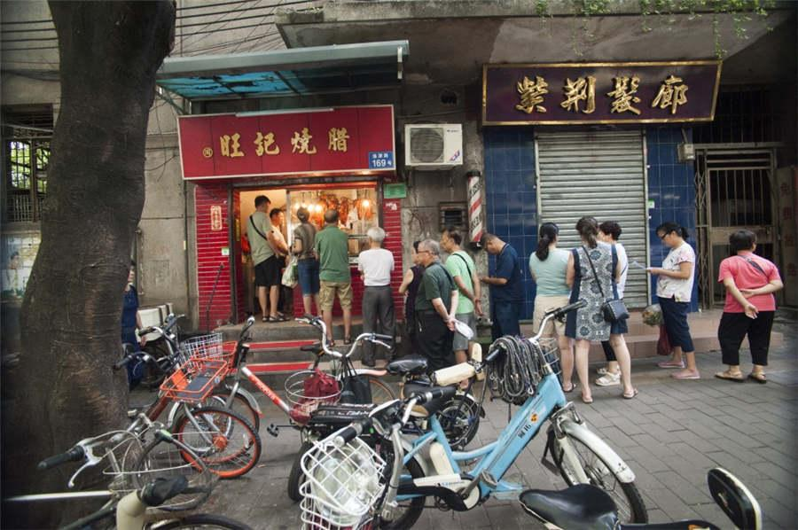 People line up in front of the cured meat shop of a time-honored brand in Liwan district of Guangzhou city in South China\'s Guangdong Province, July 31, 2018. (Photo provided to chinadaily.com.cn)