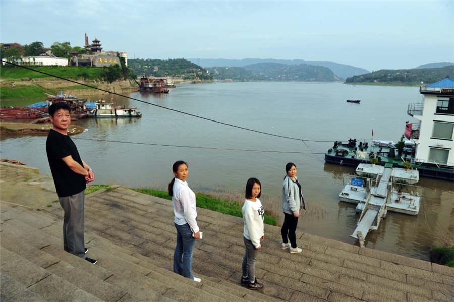 Four childhood friends take a photo years later at the riverside of the Changshou River in Chongqing, April 27, 2018.  (Photo provided to chinadaily.com.cn)