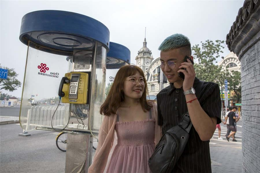 A couple walks past a deserted telephone box while the man talks on a mobile phone in Qianmen, Beijing in 2018. (Photo provided to chinadaily.com.cn)
