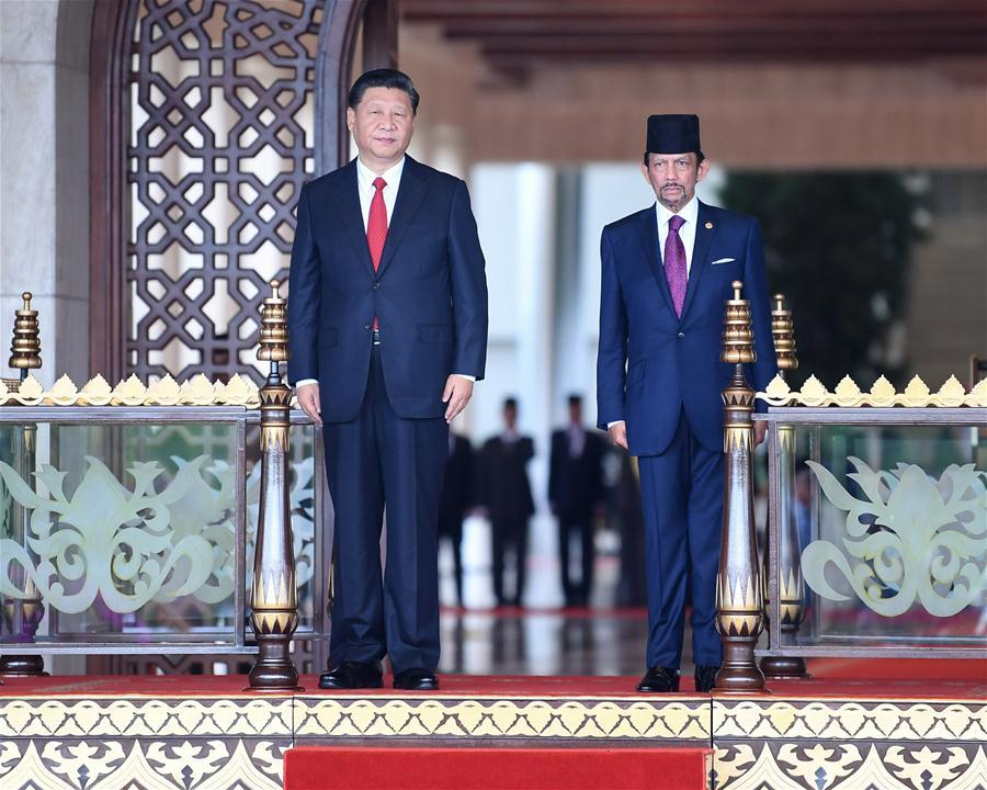 Chinese President Xi Jinping (L) attends a grand welcome ceremony held by Brunei\'s Sultan Haji Hassanal Bolkiah at Istana Nurul Iman, Brunei\'s royal palace, before their talks in Bandar Seri Begawan, Brunei, Nov. 19, 2018. (Xinhua/Yan Yan)