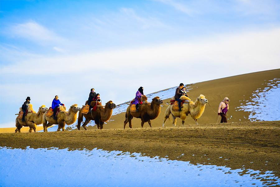 Dunhuang embraces this winter\'s first snowfall on Nov. 14. As the sun comes out, snow scenery in local landmark attractions like the Mingsha Mountain and Yueya Spring, a crescent-shaped spring-fed lake surrounded by desert, turns to a fairyland. (Photo/China Daily)