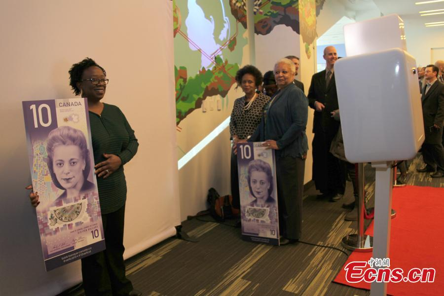 People pose for photo with a $10 banknote featuring Viola Desmond in Toronto, Canada, Nov. 19, 2018. The banknote is the first vertically oriented bill in Canada and the first regularly circulating banknote to feature a Canadian woman, civil rights advocate Viola Desmond, on the front. (Photo: China News Service/Yu Dongrui)