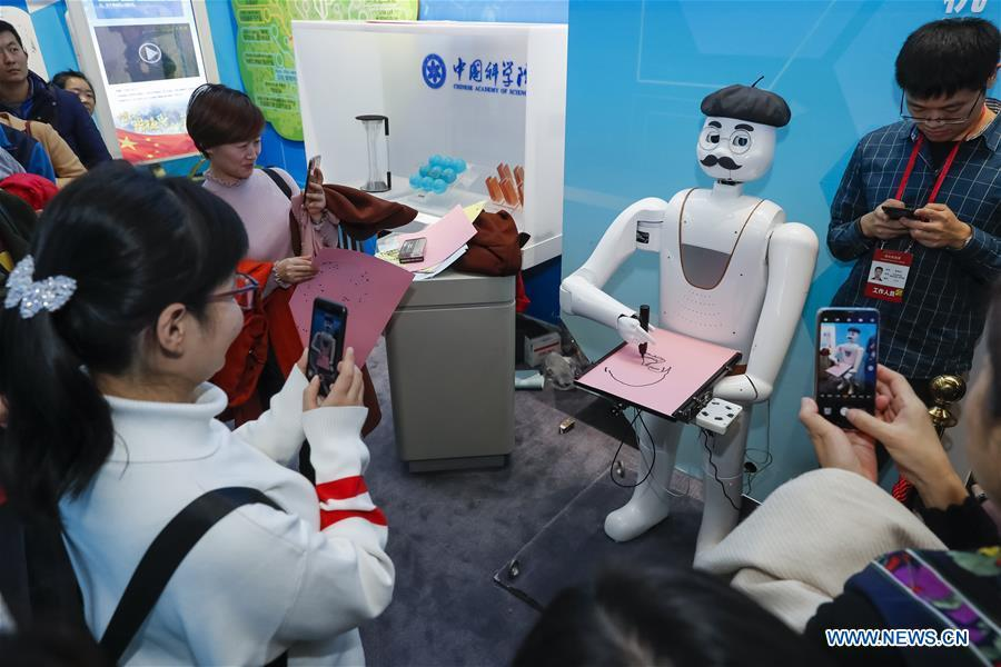An intelligent painting robot with facial recognition function draws a portrait during a major exhibition to commemorate the 40th anniversary of China\'s reform and opening-up at the National Museum of China in Beijing, capital of China, Nov. 20, 2018. It can finish a portrait within three to five minutes. (Xinhua/Shen Bohan)