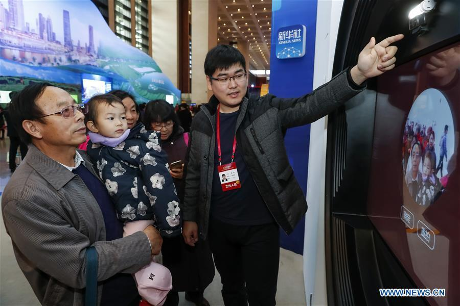 Visitors experience a musical interactive project of Xinhua News Agency during a major exhibition to commemorate the 40th anniversary of China\'s reform and opening-up at the National Museum of China in Beijing, capital of China, Nov. 20, 2018. The project generated pop music of different periods on the basis of gender and facial recognition. (Xinhua/Shen Bohan)