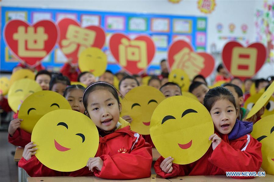 Children show greeting cards made to mark the World Hello Day which falls on Nov. 21 annually at the experimental primary school at Baokang County, central China\'s Hubei Province. (Xinhua/Yang Tao)