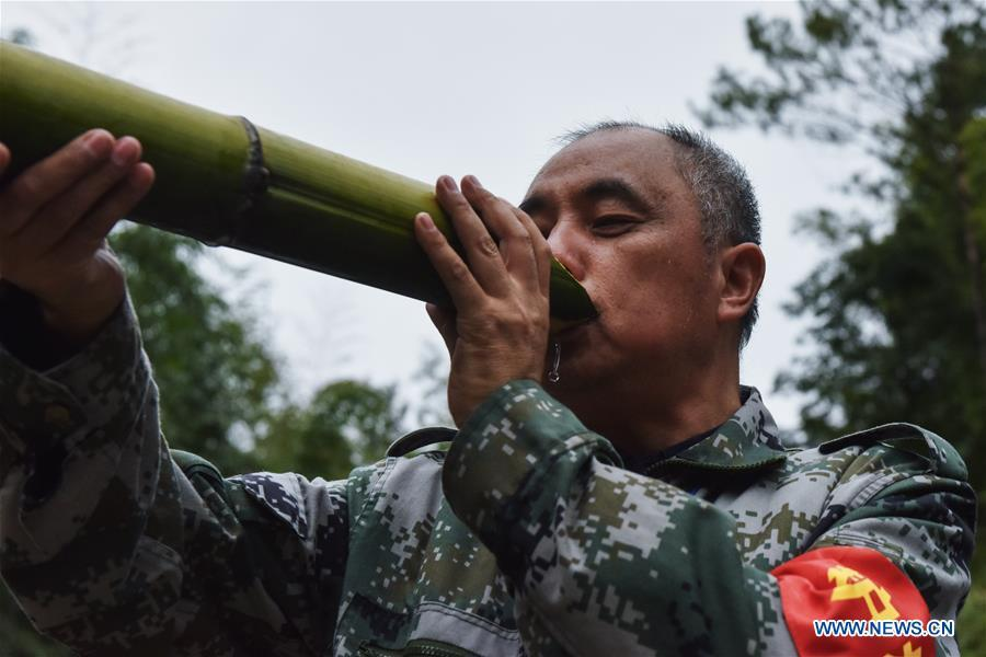 Forest ranger Tang Xiaoping drinks in a bamboo forest at Hushi forestry farm in Chishui City, southwest China\'s Guizhou Province, Oct. 24, 2018. Chishui is famous for its bamboo forest. To guard the bamboo, forest rangers need to patrol for all year round. At the Hushi forestry farm, there is a patrol group consisting of a dozen of forest rangers. They are in charge of about an area of 2,400 hectares. Loneliness is one of the difficulties they need to face as they can only go back home after one-week work. But all of them stay to keep working after those years as they love the bamboo forest and are determined to guard it. (Xinhua/Li Mangmang)