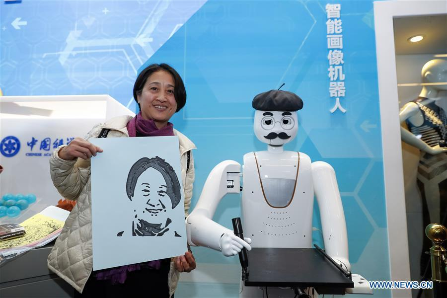 A visitor shows a portrait drawn by an intelligent painting robot with facial recognition function during a major exhibition to commemorate the 40th anniversary of China\'s reform and opening-up at the National Museum of China in Beijing, capital of China, Nov. 20, 2018. It can finish a portrait within three to five minutes. (Xinhua/Shen Bohan)