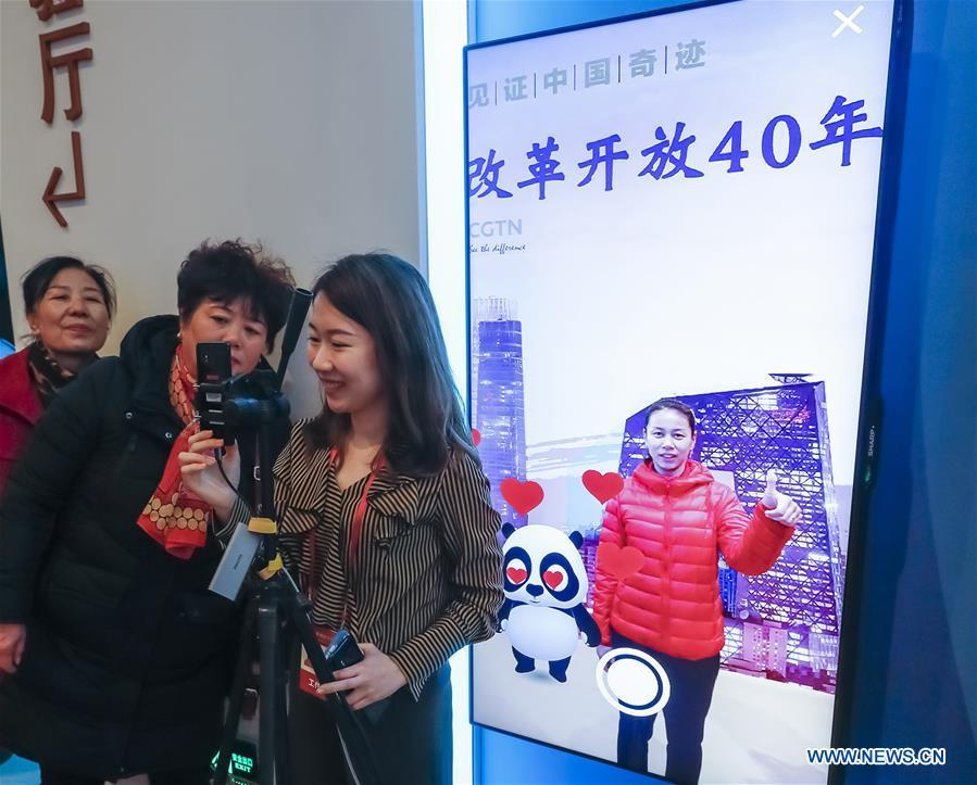 Visitors interact with a virtual panda of augmented reality (AR) experience project and pose for photo during a major exhibition to commemorate the 40th anniversary of China\'s reform and opening-up at the National Museum of China in Beijing, capital of China, Nov. 20, 2018. (Xinhua/Shen Bohan)