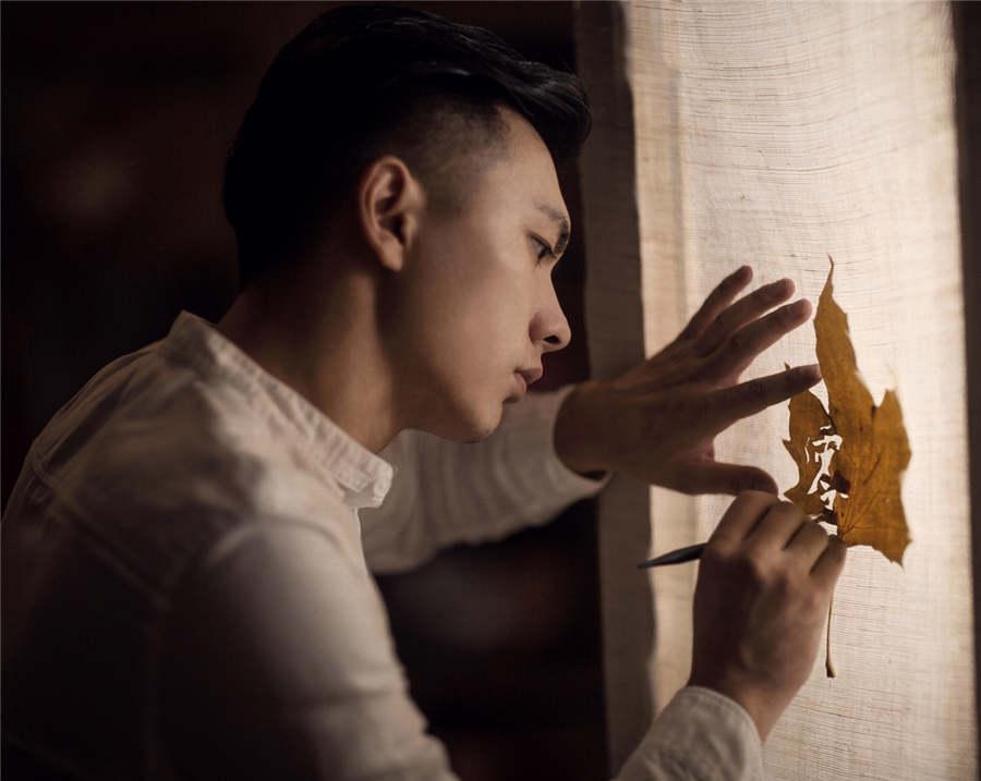Artist Ding Li works on leaf art.  (Photo provided to chinadaily.com.cn)