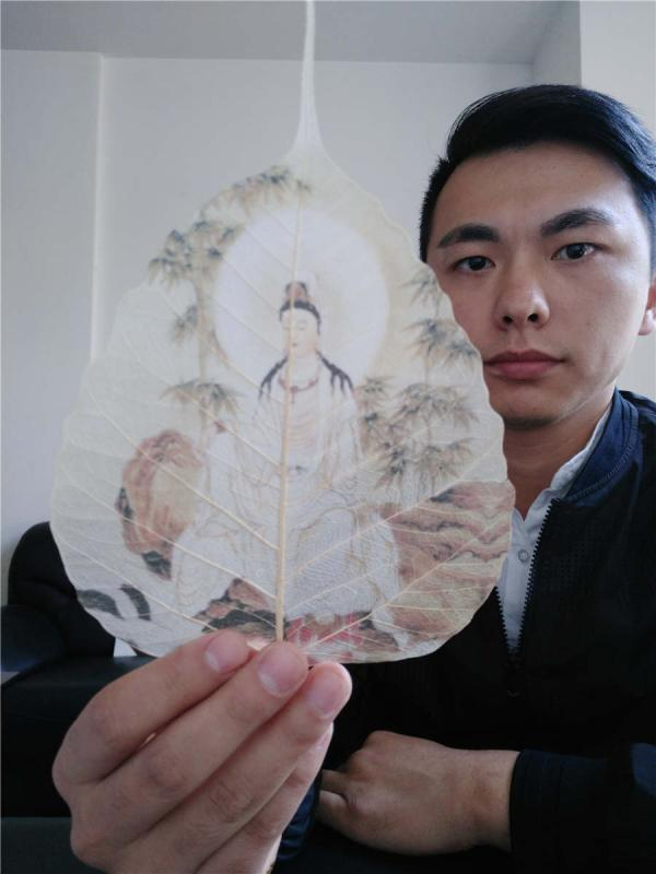 Ding Li takes a selfie with his artwork in his workshop in Xianning city, Hubei Province. (Photo provided to chinadaily.com.cn)  Leaf painting has a history of more than 2,000 years in China. A 27-year-old man Ding Li, from Xianning city of Hubei Province has devoted a dozen years to learning leaf art, and fuses ancient tattooing techniques into his creations. Ding has spent one year creating the ancient painting Along the River During the Qingming Festival which is painted on 10 pieces of michelia alba leaves.  Ding started to learn painting at 5, and began learning carving at 12. When he first found out about leaf painting at 13 years old, he became obsessed with the art.  The process of making leaf paintings is quite complicated. First the artist selects fine linden leaves or michelia alba leaves from mountains in Yunnan province, then go through over 60 steps such as cutting, soaking, pressing, sculpting, grinding, ironing and bleaching. The whole affair takes at least two to three months to finish.  Two of Ding\'s works won the silver award during a recent art exhibition between China and Japan on Oct. 28.  Before each creation, Ding will first learn related historical stories to make his artwork more detailed. \