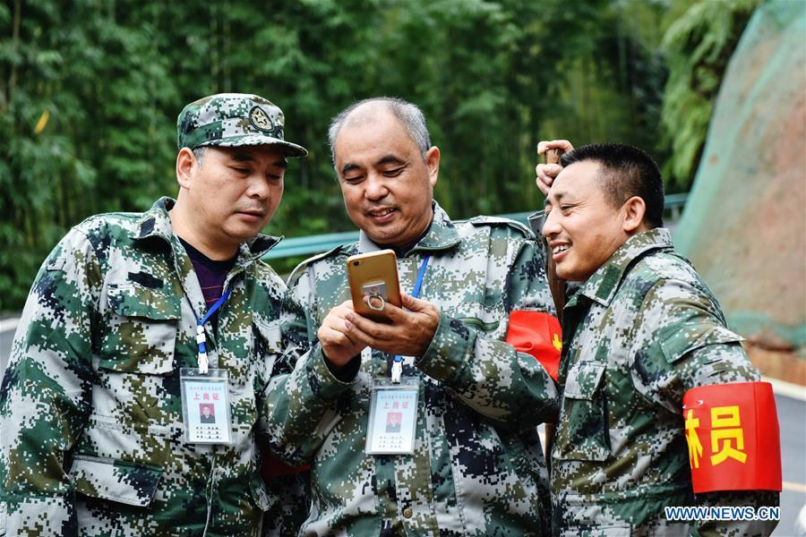 Forest ranger Tang Xiaoping (C) shows his photos of family members with colleagues at Hushi forestry farm in Chishui City, southwest China\'s Guizhou Province, Oct. 24, 2018. Chishui is famous for its bamboo forest. To guard the bamboo, forest rangers need to patrol for all year round. At the Hushi forestry farm, there is a patrol group consisting of a dozen of forest rangers. They are in charge of about an area of 2,400 hectares. Loneliness is one of the difficulties they need to face as they can only go back home after one-week work. But all of them stay to keep working after those years as they love the bamboo forest and are determined to guard it. (Xinhua/Li Mangmang)