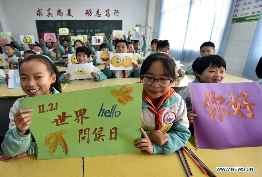 Children show greeting cards made to mark the World Hello Day which falls on Nov. 21 annually at a center primary school at Yangguantun Township of Chiping County, east China\'s Shandong Province. (Xinhua/Zhao Yuguo)