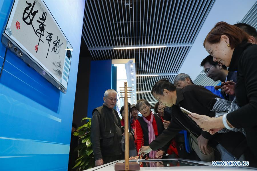 The 64-year-old Huang Chengchu from central China\'s Hunan Province experience an intelligent calligraphy exhibit during a major exhibition to commemorate the 40th anniversary of China\'s reform and opening-up at the National Museum of China in Beijing, capital of China, Nov. 20, 2018. (Xinhua/Shen Bohan)