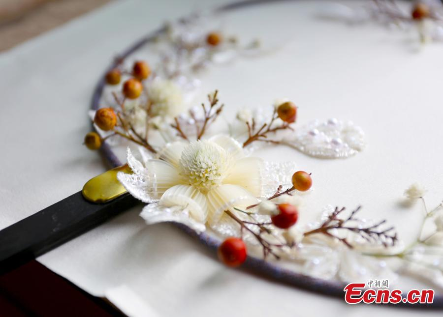 Liu Yao, a girl from northwestern China city Lanzhou, shows her embroidery works featuring patterns made of preserved flowers. With stitching techniques of Suzhou Embroidery and beading skills, the girl, an embroidery lover, makes her works with colorful dried flowers. (Photo: China News Service/ Gao Zhan)