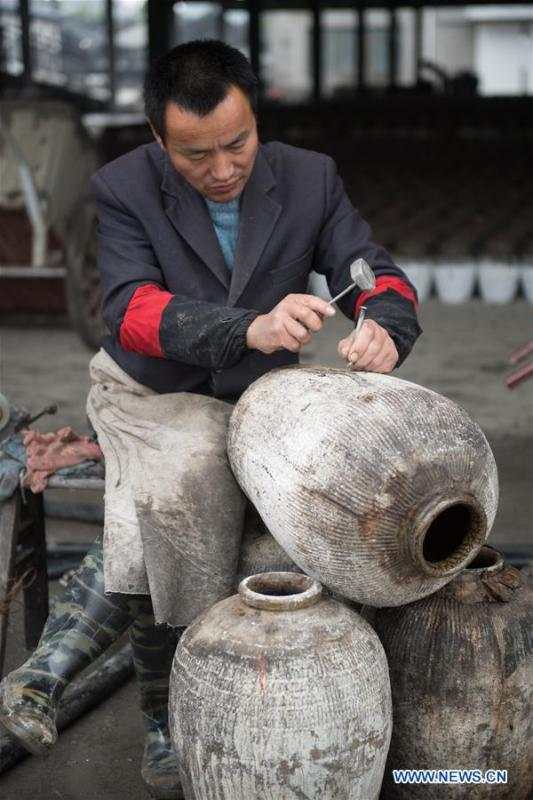 A worker repairs a rice wine jar at Shaoxing Nuerhong Winery Company in Shaoxing, east China\'s Zhejiang Province, Nov. 21, 2018. The company maintains its traditional rice wine brewing method, which is composed of nearly 20 processing steps. (Xinhua/Weng Xinyang)