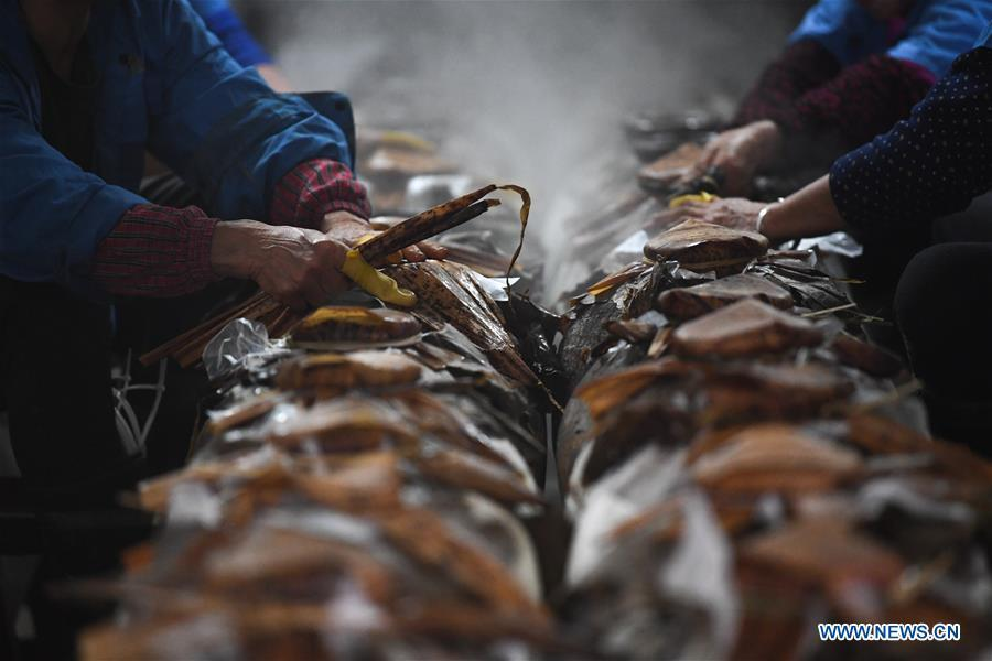 Workers seal the rice wine jars with leaves of lotus and bamboo at Shaoxing Nuerhong Winery Company in Shaoxing, east China\'s Zhejiang Province, Nov. 21, 2018. The company maintains its traditional rice wine brewing method, which is composed of nearly 20 processing steps. (Xinhua/Weng Xinyang)