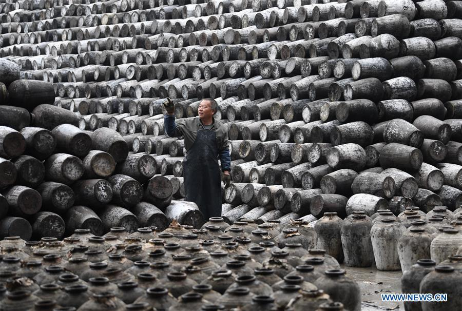 A worker checks the jars used to contain rice wine at Shaoxing Nuerhong Winery Company in Shaoxing, east China\'s Zhejiang Province, Nov. 21, 2018. The company maintains its traditional rice wine brewing method, which is composed of nearly 20 processing steps. (Xinhua/Weng Xinyang)