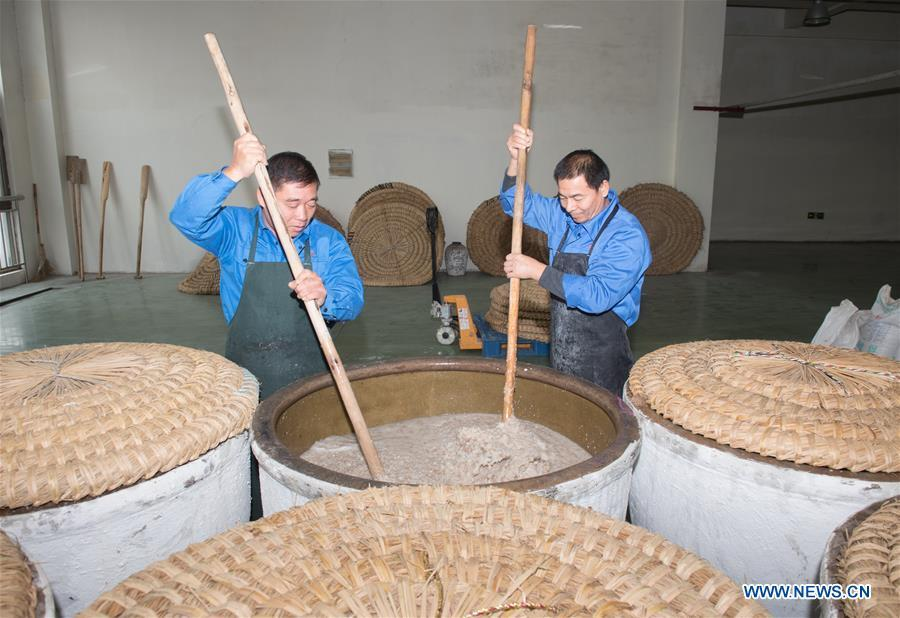 Workers stir the cooked rice to make wine at Shaoxing Nuerhong Winery Company in Shaoxing, east China\'s Zhejiang Province, Nov. 21, 2018. The company maintains its traditional rice wine brewing method, which is composed of nearly 20 processing steps. (Xinhua/Weng Xinyang)