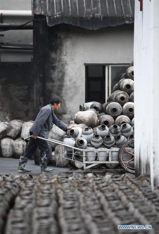 A worker coveys the jars used to contain rice wine at Shaoxing Nuerhong Winery Company in Shaoxing, east China\'s Zhejiang Province, Nov. 21, 2018. The company maintains its traditional rice wine brewing method, which is composed of nearly 20 processing steps. (Xinhua/Weng Xinyang)