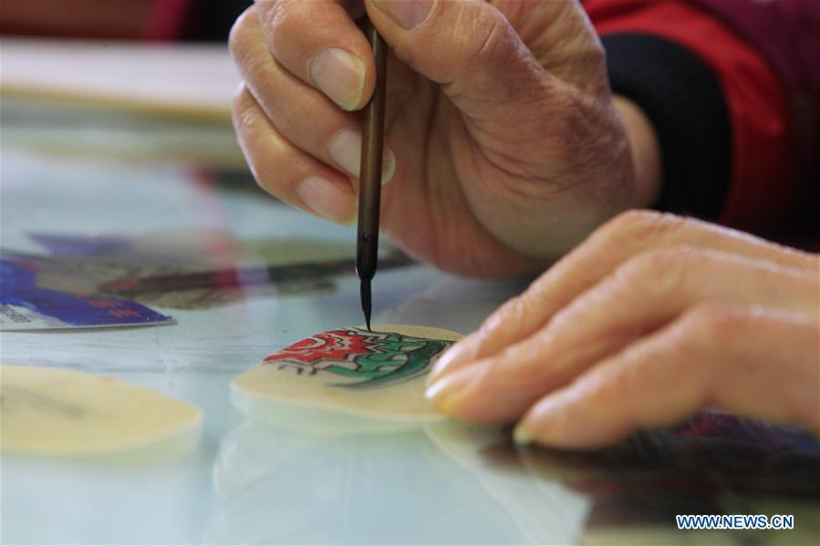 Zhang Kunrong paints on a shadow puppetry piece in Haining City, east China\'s Zhejiang Province, Nov. 20, 2018. Zhang Kunrong, 79, a locally born shadow puppetry player, is an inheritor of the Haining shadow puppetry, a form of traditional theatre acted by colorful silhouette figures made from leather or paper, accompanied by music and singing. A typical variety popular in south China, Haining shadow puppetry, a national intangible cultural heritage, has a history of about 900 years dating back to the Southern Song Dynasty (AD 1127-1279). Obsessed with the shadow play since childhood, Zhang Kunrong was recruited to the provincial shadow puppetry troupe in 1958 and soon became a mainstay after two year\'s practice and in the later years staged performances at home and abroad as Haining shadow puppetry grows popular. Nowadays, Zhang works more on script writing, directing and teaching apprentices. Haining shadow puppetry was listed as one of the state-level intangible cultural heritages in 2006 and was included in the UNESCO Intangible Cultural Heritage of Humanity list in 2011. (Xinhua/Sui Xiankai)