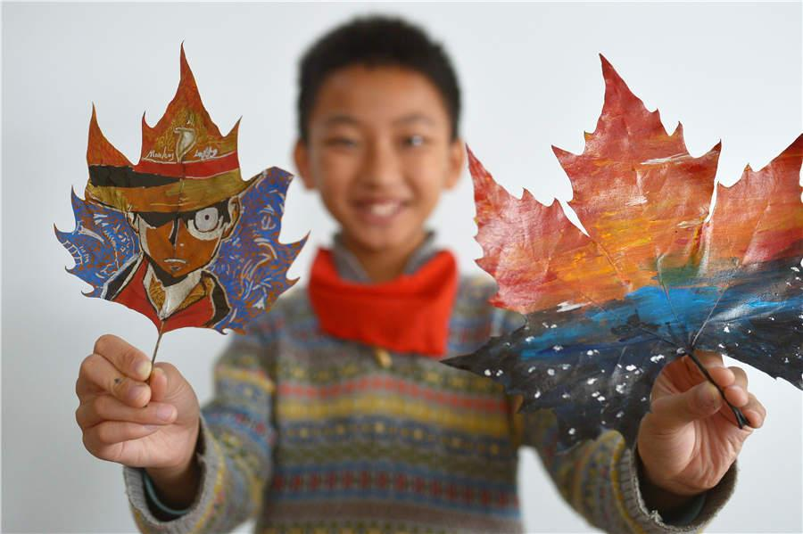 A student shows his leaf art at a primary school in Qingdao, East China\'s Shandong Province, on Nov. 19, 2018. (Photo/Asianewsphoto)
