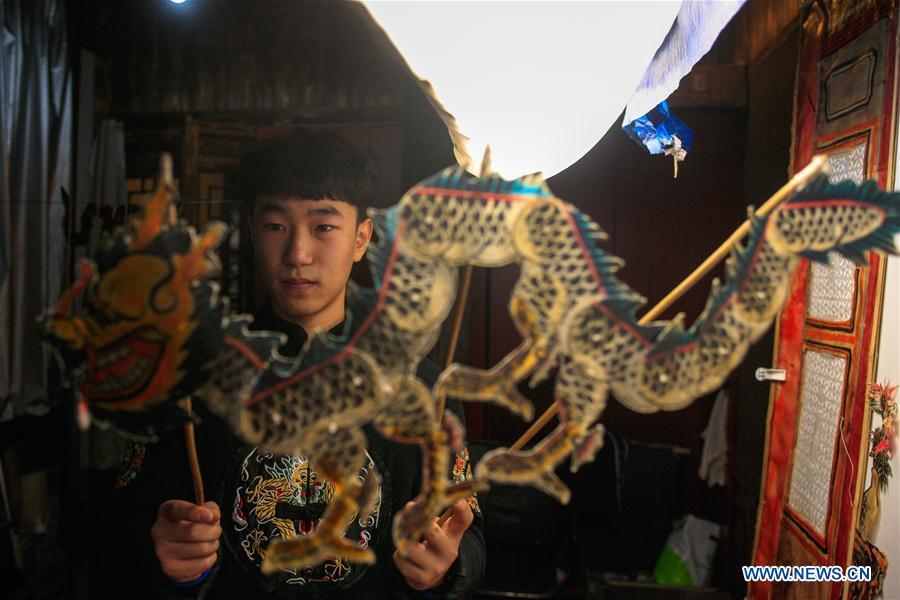 Liu Fan, one of Zhang Kunrong\'s apprentices, prepares before a shadow puppetry show in Haining City, east China\'s Zhejiang Province, Nov. 21, 2018. Zhang Kunrong, 79, a locally born shadow puppetry player, is an inheritor of the Haining shadow puppetry, a form of traditional theatre acted by colorful silhouette figures made from leather or paper, accompanied by music and singing. A typical variety popular in south China, Haining shadow puppetry, a national intangible cultural heritage, has a history of about 900 years dating back to the Southern Song Dynasty (AD 1127-1279). Obsessed with the shadow play since childhood, Zhang Kunrong was recruited to the provincial shadow puppetry troupe in 1958 and soon became a mainstay after two year\'s practice and in the later years staged performances at home and abroad as Haining shadow puppetry grows popular. Nowadays, Zhang works more on script writing, directing and teaching apprentices. Haining shadow puppetry was listed as one of the state-level intangible cultural heritages in 2006 and was included in the UNESCO Intangible Cultural Heritage of Humanity list in 2011. (Xinhua/Zhu Weixi)