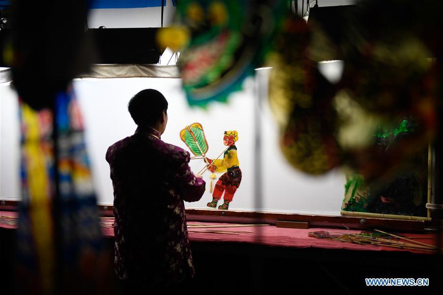 Zhang Kunrong performs in a shadow puppetry show in Haining City, east China\'s Zhejiang Province, Nov. 20, 2018. Zhang Kunrong, 79, a locally born shadow puppetry player, is an inheritor of the Haining shadow puppetry, a form of traditional theatre acted by colorful silhouette figures made from leather or paper, accompanied by music and singing. A typical variety popular in south China, Haining shadow puppetry, a national intangible cultural heritage, has a history of about 900 years dating back to the Southern Song Dynasty (AD 1127-1279). Obsessed with the shadow play since childhood, Zhang Kunrong was recruited to the provincial shadow puppetry troupe in 1958 and soon became a mainstay after two year\'s practice and in the later years staged performances at home and abroad as Haining shadow puppetry grows popular. Nowadays, Zhang works more on script writing, directing and teaching apprentices. Haining shadow puppetry was listed as one of the state-level intangible cultural heritages in 2006 and was included in the UNESCO Intangible Cultural Heritage of Humanity list in 2011. (Xinhua/Huang Zongzhi)