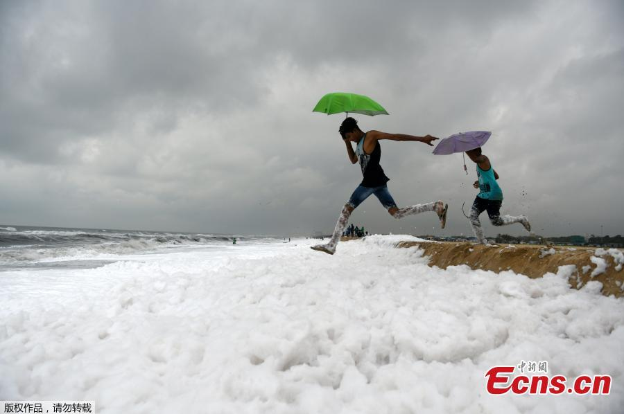 Umbrella-toting Indian youths jump over foamy discharge, caused by pollutants, as it mixes with the surf at a beach in Chennai on November 22, 2018. - High levels of sewage and industrial waste was claimed to be the cause of the foam, officials said. (Photo/Agencies)