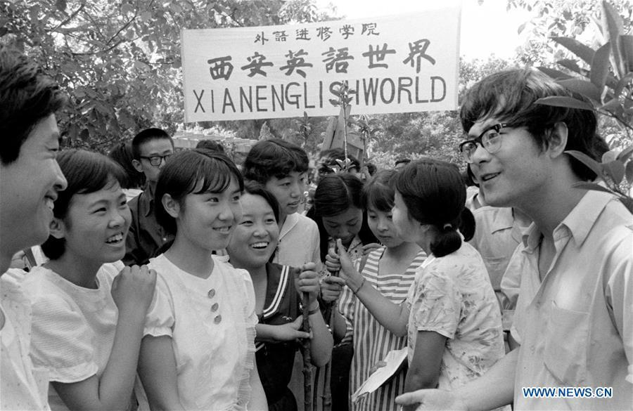 File photo taken in 1985 shows people practicing English in Xi\'an, northwest China\'s Shaanxi Province. From 1978 when China started its reform and opening-up policy, a door to the outside world has been opened. Along with the imported commodities, fashion ideas inevitably slipped into China and since then the country, which was somewhat lack of fashion diversity, started its journey to pursue fashions. Over the past four decades, the thirst for beauty has driven Chinese people to pursue every possible fashionable element. The change first came with dress when colorful and diversified clothing prevailed as against the former dominant blue and grey. For a time, men and women raced to hairdressers\' just for trendy hairdos. Eating McDonald\'s or western cuisine even once was regarded as a fashionable thing. However, the most conspicuous change is that Chinese people have become more inclusive and they tend to accept new fashions, styles and concepts. China nowadays is dazzling the world not only on the fashion stage but in many other fields. Changes in fashions, as a profile of society, has well interpreted the benefits to people brought by China\'s reform and opening-up policy. (Xinhua)